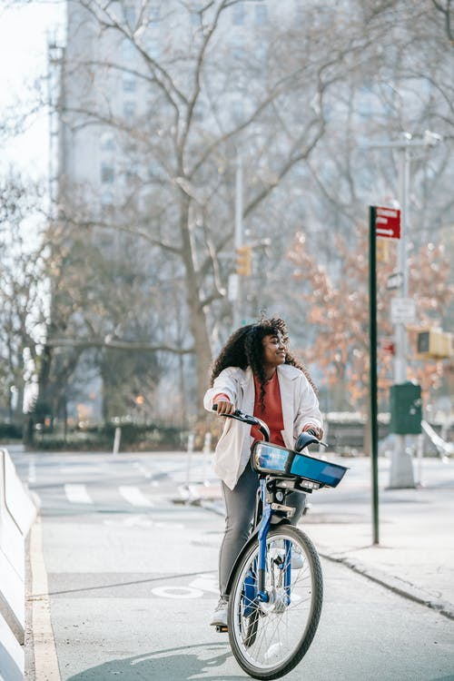 Full body cheerful African American female with long curly hair riding bicycle on city street on early spring day
