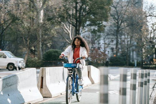 Cheerful black woman riding bicycle on city street