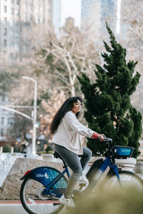 Side view full length of young black lady in casual outfit riding bicycle on road in town on street near trees and buildings in sunny day