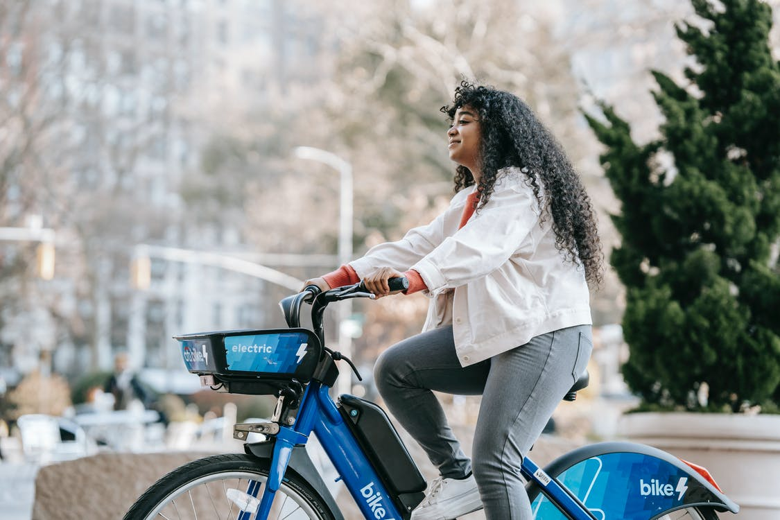 Side view of positive African American lady wearing casual clothes while riding bike in town in park in sunny day near buildings and trees
