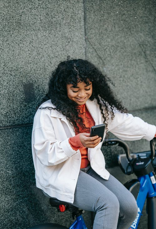 Positive black woman sitting on bicycle with phone near fence