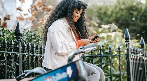 African American female with smartphone sitting on bench near bike