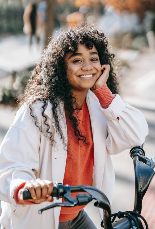 Happy black woman with bicycle standing on sunny street