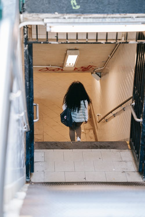 Back view anonymous female with long curly hair going downstairs in underground pedestrian passage