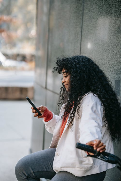 Side view glad African American female with fine curly hair sitting on bicycle and using mobile phone on sunny city street