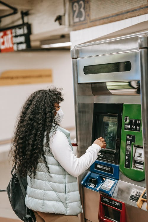 Back view attentive African American female with fine curly hair buying metro tickets via ticketing machine in underground hallway