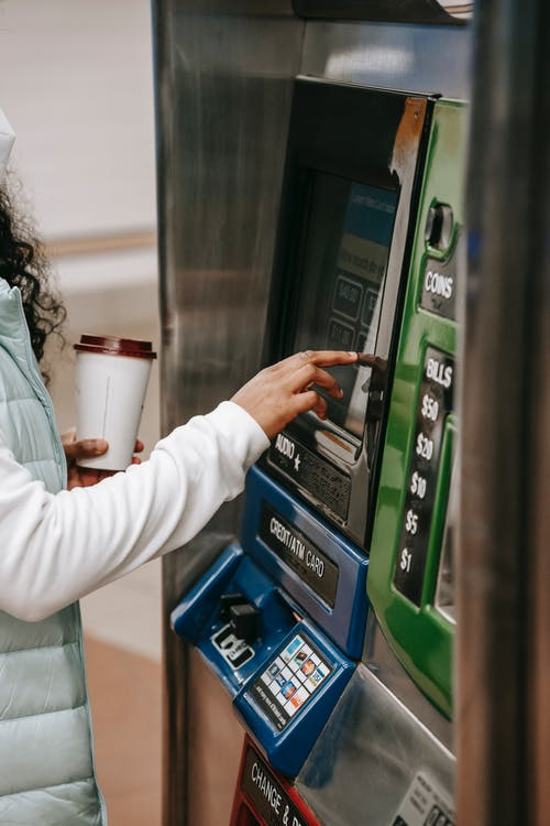 Crop anonymous African American female with takeaway coffee wearing casual outfit pressing soft buttons on ticket machine in underground station