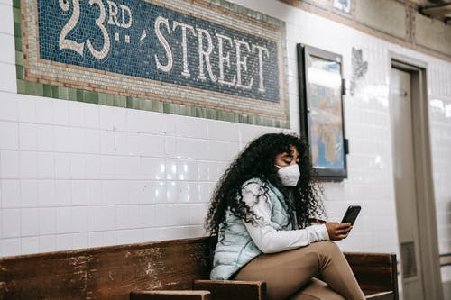 Focused African American female in casual clothes browsing mobile phone while sitting on bench in New York underground platform