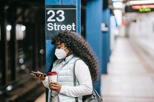 Focused African American female wearing casual outfit and protective mask standing on New York underground platform with takeaway coffee and using mobile phone