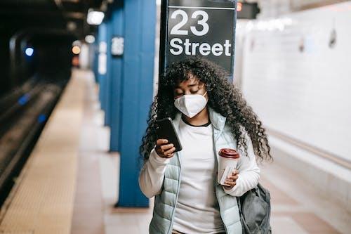 Focused black woman using smartphone on metro platform