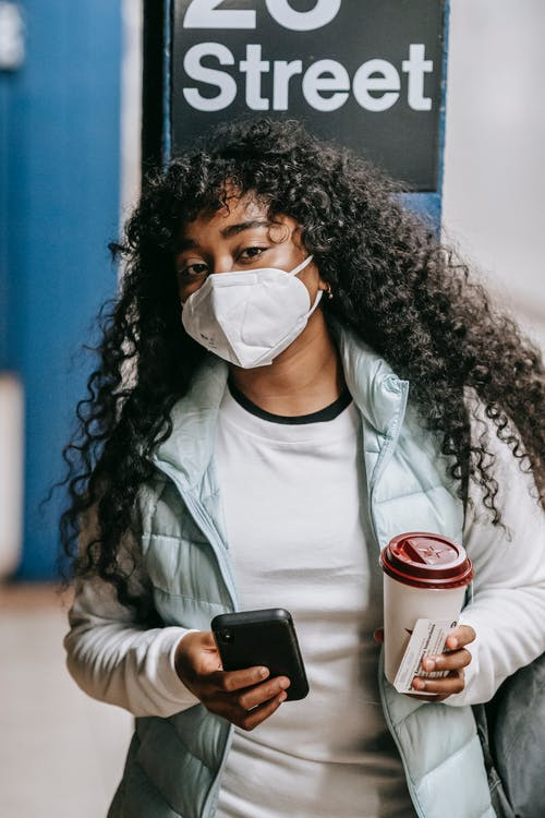 Emotionless African American female in casual clothes and respirator standing with takeaway coffee and smartphone on New York underground platform and looking at camera