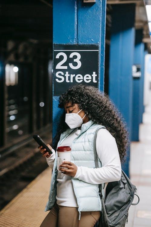 Black woman using smartphone on underground platform