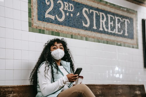 Emotionless African American female in casual wear and protective mask using mobile phone and looking away while sitting on bench in metro station platform in New York