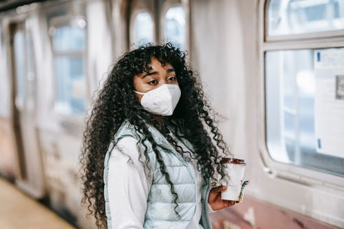 Black woman in mask waiting to enter subway train
