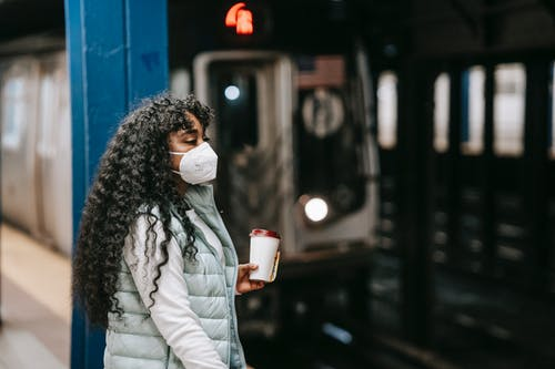 Calm African American female in casual outfit and protective mask standing on underground platform near arriving train