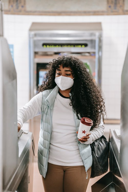Thoughtful African American female in casual wear and face mask with takeaway coffee swiping ticket on turnstile in subway station