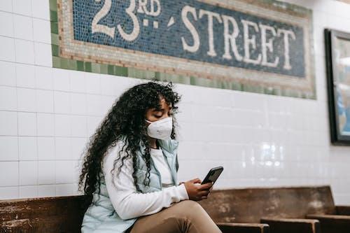 Focused black woman using smartphone in underground station
