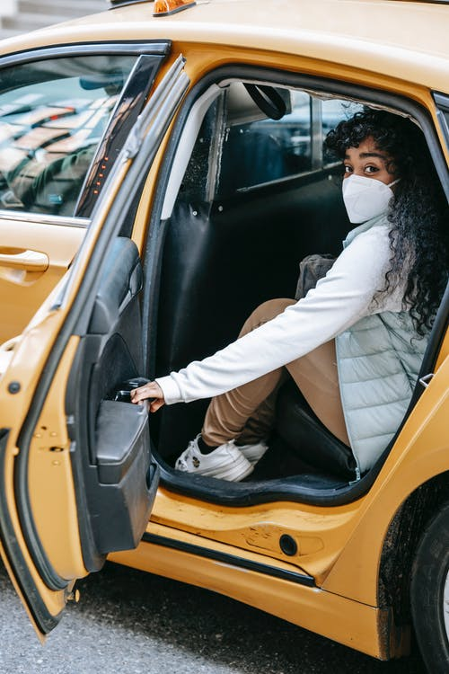 Trendy young black lady sitting in taxi