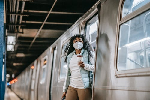Young African American female passenger in casual clothes and mask drinking takeaway coffee and getting off train in subway station