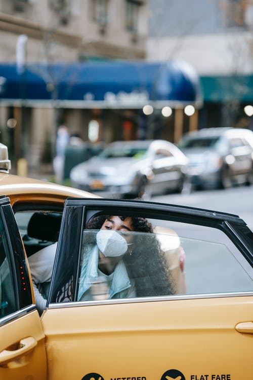 Unrecognizable ethnic woman in mask getting into cab in city