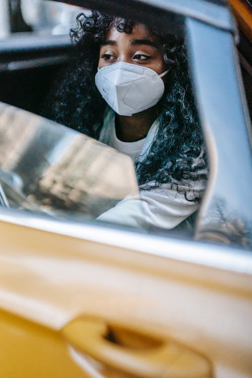 Calm black female in mask sitting in yellow taxi and looking away