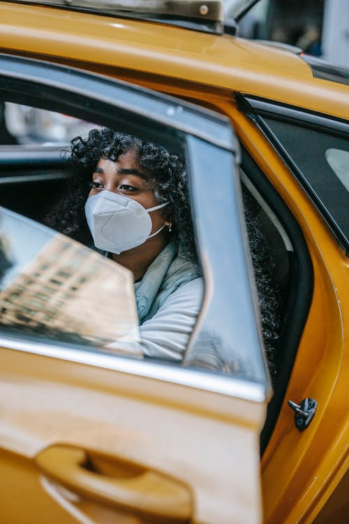 Young black lady in casual clothes and protective mask in yellow cab with open door and window in daytime in street in town