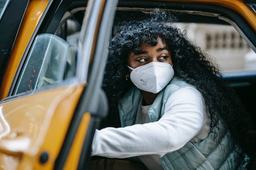 African American woman in mask in taxi on street