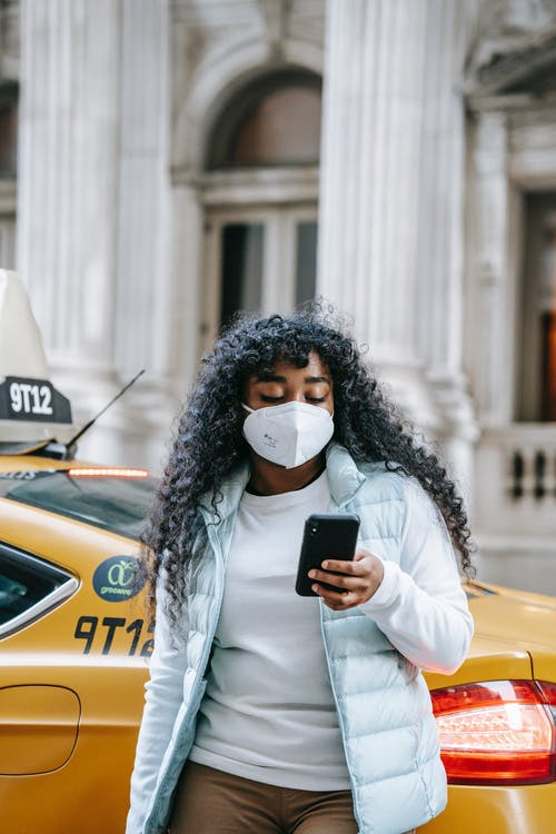 African American woman in mask using smartphone near taxi