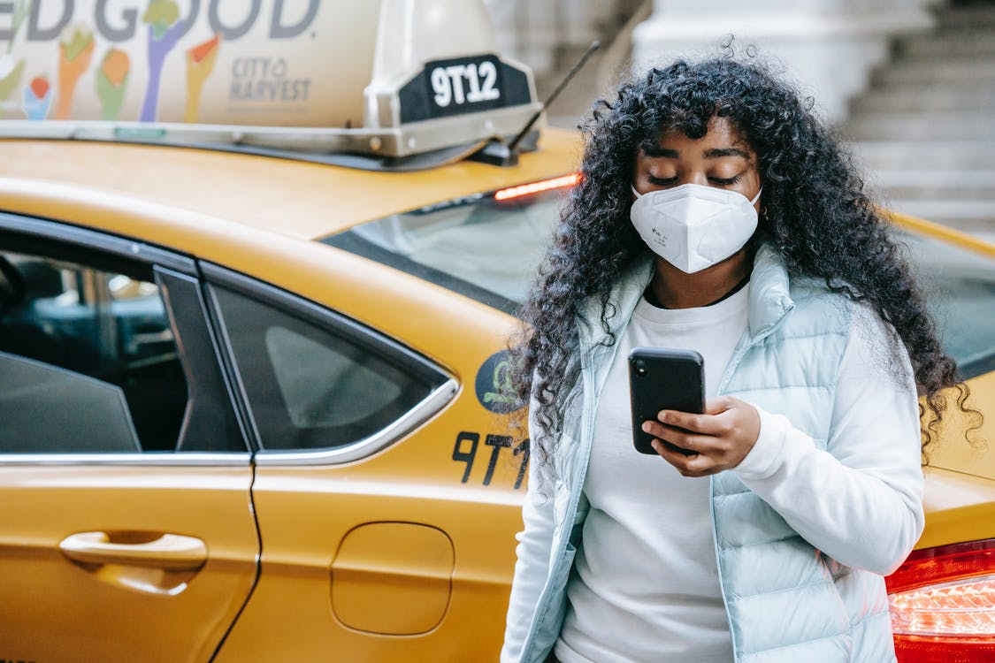 Black female with phone in mask near cab in city