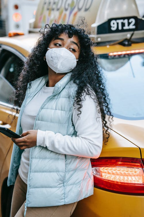 Young black lady wearing protective mask and casual clothes while leaning on yellow cab and browsing on phone in city street in daytime and looking away thoughtfully