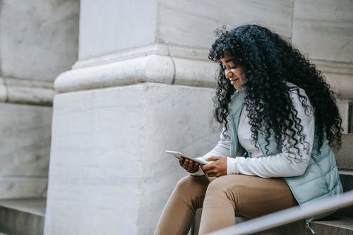 Happy young African American woman wearing casual clothes while surfing on tablet and sitting on stone stairs near building with columns in street in town in daylight