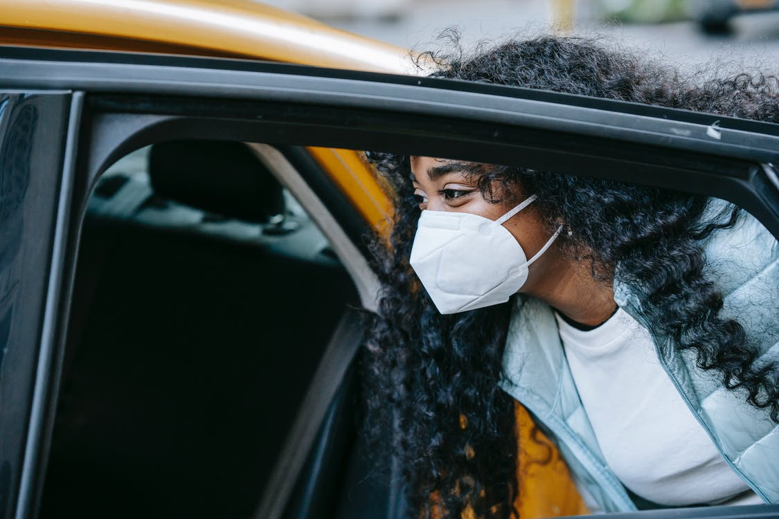 Black female in mask getting cab on city street
