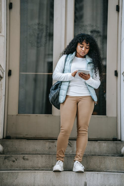 Serious black lady browsing on tablet on steps near building