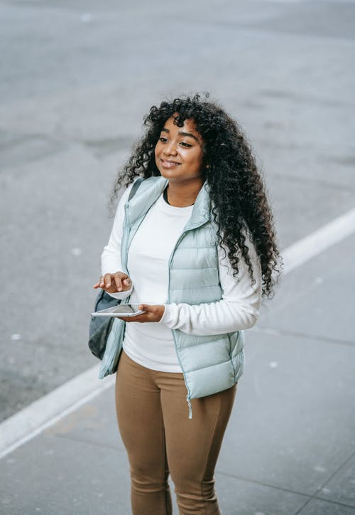 Positive young African American lady in casual outfit using tablet while standing on city street on pavement near asphalt road in daylight