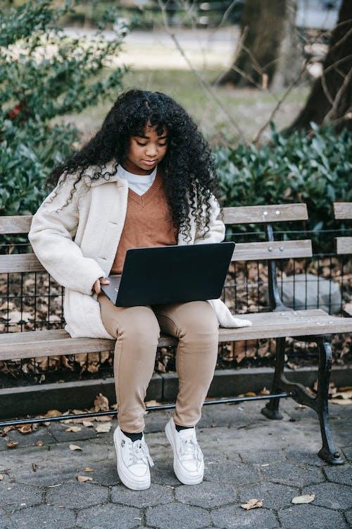 Mulher De Casaco Branco Sentada Em Um Banco De Madeira Marrom Usando Um Laptop
