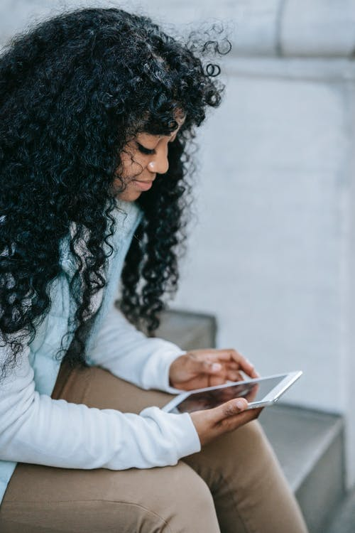 Pensive young African American woman wearing casual clothes while surfing on tablet and sitting on stone stairs near building in daylight in street in town