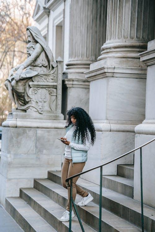 Beton Heykelin Yanında Duran Beyaz Gömlek Ve Mavi Kot şortlu Kadın