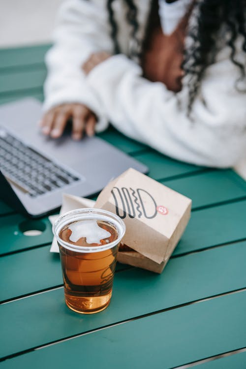 Crop anonymous African American female browsing netbook while sitting at table with burger in paper pack and plastic glass of cold beer