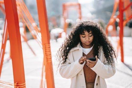 Kostenloses Stock Foto zu afroamerikaner-frau, app, blick auf den bildschirm
