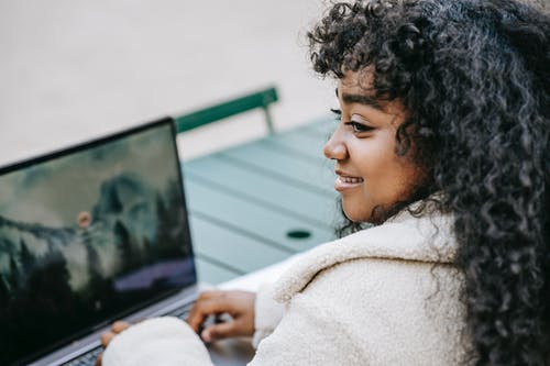 Cheerful black woman browsing laptop in city park