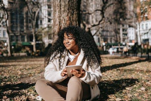 Smartphone Kullanırken Yerde Oturan Beyaz önlüklü Kadın