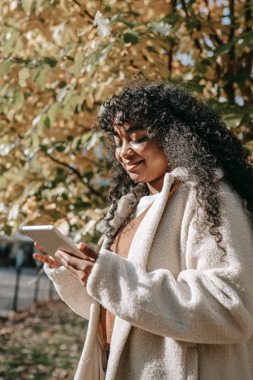 Cheerful African American female in white warm coat browsing tablet while standing in sunny city park on warm autumn day