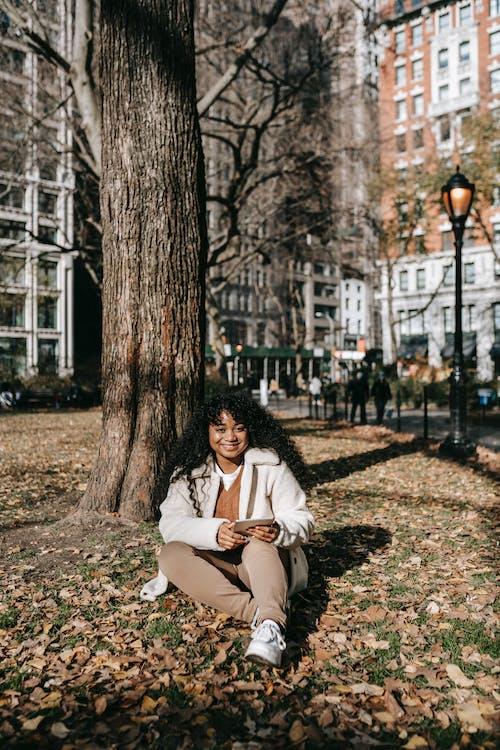 Çıplak Ağaçların Yanında Yerde Oturan Beyaz önlüklü Kadın