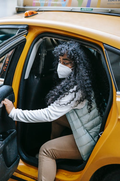 Side view emotionless African American female in warm clothes and face mask opening door and getting off yellow taxi