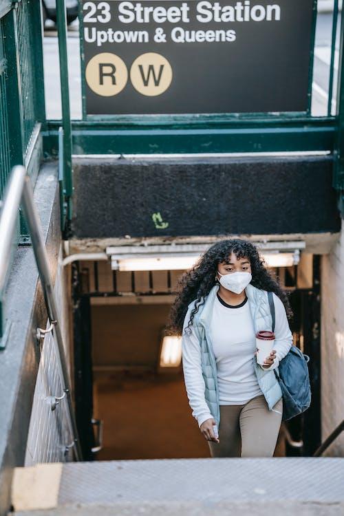 Black woman in respirator leaving metro station