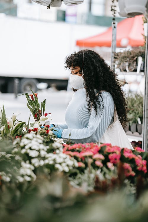 Black woman choosing flowers in street shop