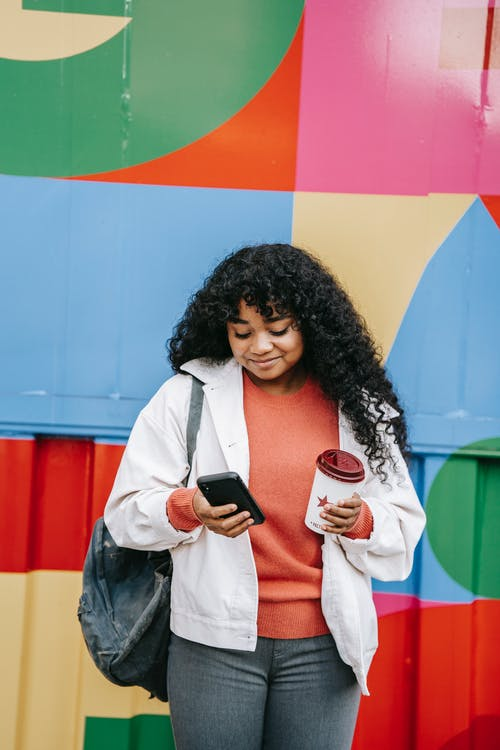 Smiling black woman using smartphone near colorful wall