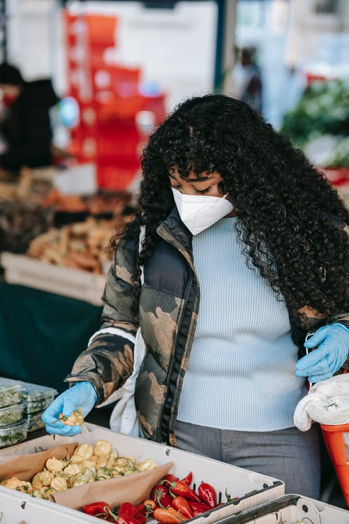 African American female buyer in protective mask and gloves picking vegetable from box at counter while shopping in local street market