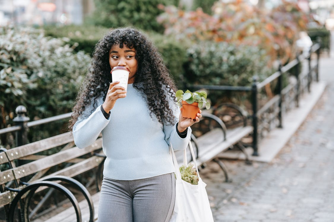 Content black woman with flowerpot drinking coffee
