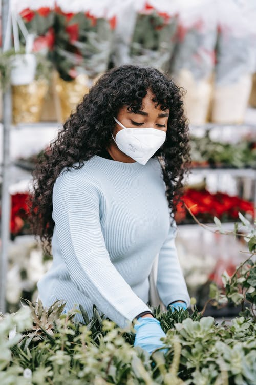 African American female wearing protective mask and gloves picking fresh flowers while standing in floral market with blooming bouquets on blurred background